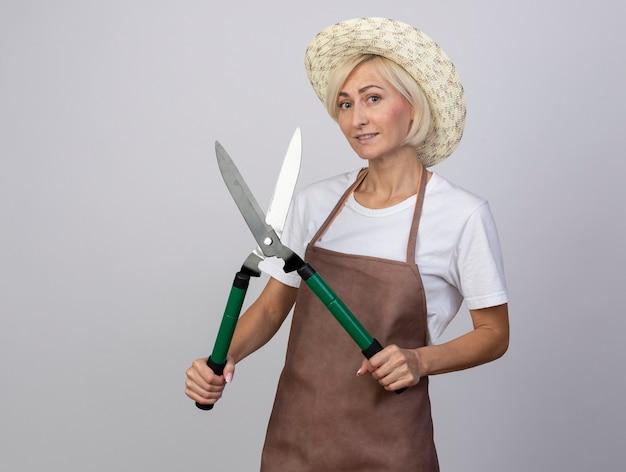 Glimlachende blonde tuinmanvrouw van middelbare leeftijd in uniform met hoed met heggenschaar geïsoleerd op een witte muur met kopieerruimte