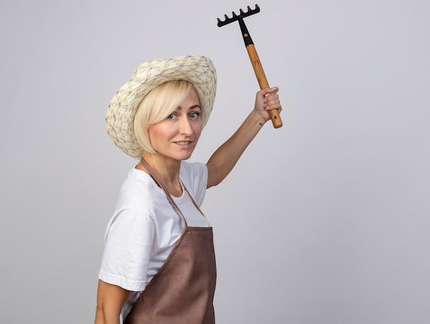 Glimlachende blonde tuinmanvrouw van middelbare leeftijd in uniform met hoed