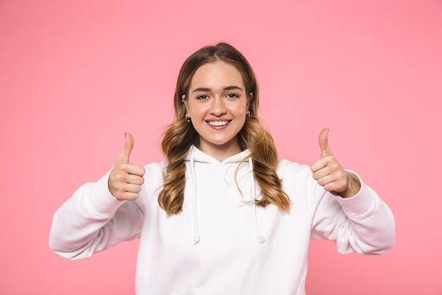 Glimlachende blonde vrouw die in vrijetijdskleding draagt die duimen toont en de voorzijde over roze muur bekijkt