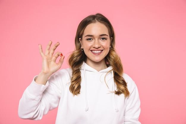 Glimlachende blonde vrouw die in vrijetijdskleding draagt die ok teken toont en de voorzijde over roze muur bekijkt