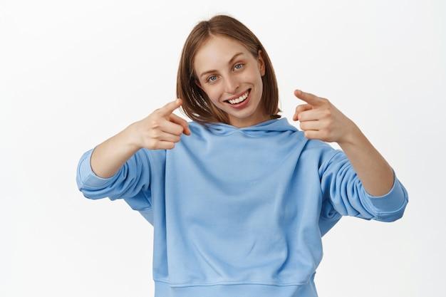 Glimlachende blonde vrouw die met de vingers naar voren wijst met een blij trots gezicht, lof en compliment, mensen uitnodigen, wenken om zich bij het gezelschap aan te sluiten, staande tegen de witte muur.