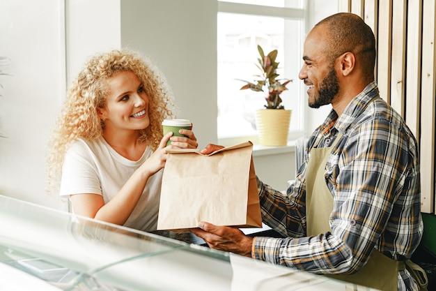 Glimlachende blonde vrouw die met een ober van een coffeeshop aan het loket spreekt