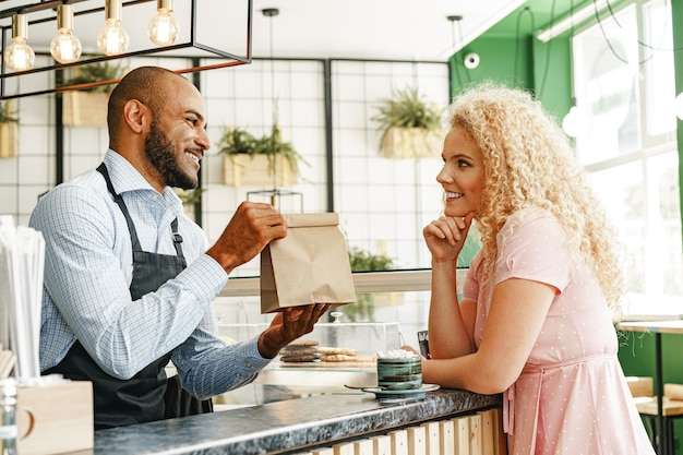 Glimlachende blonde vrouw die met een ober van een coffeeshop spreekt