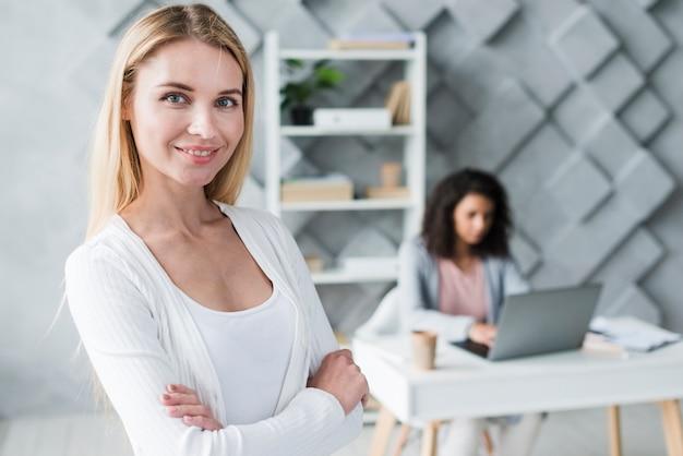Glimlachende blonde vrouw en werkende etnische collega