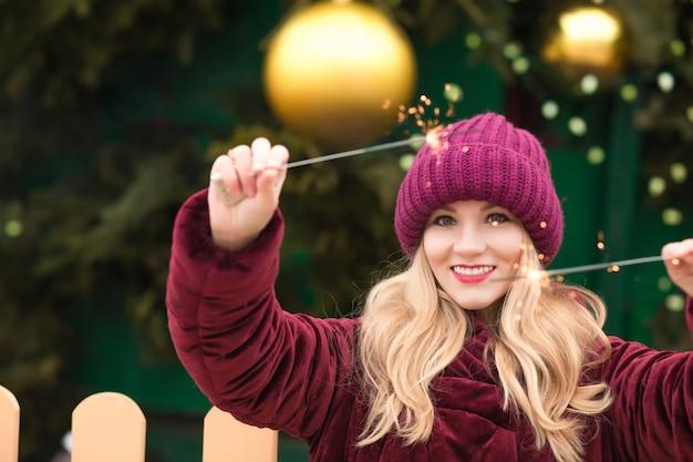 Glimlachende blonde vrouw gekleed in rode gebreide muts en warme jas met gloeiende sterretjes bij de kerstboom