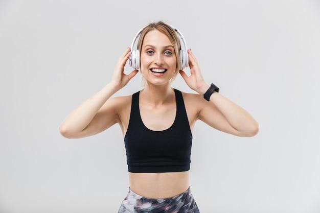 Glimlachende blonde vrouw gekleed in sportkleding luisteren naar muziek met koptelefoon tijdens training in sportschool geïsoleerd over witte muur