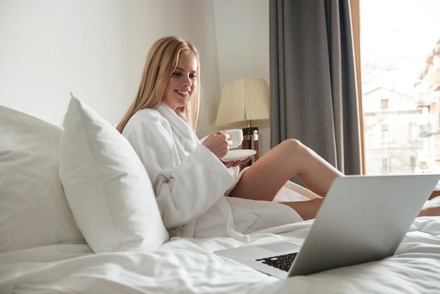Glimlachende blonde vrouw in de kop van de badjasholding van koffie