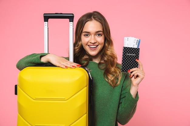Glimlachende blonde vrouw in groene trui poserend met bagage en paspoort met kaartjes vasthoudend terwijl ze naar de voorkant over roze muur kijkt