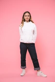 Glimlachende blonde vrouw in vrijetijdskleding poseren en kijken naar de voorkant over roze muur