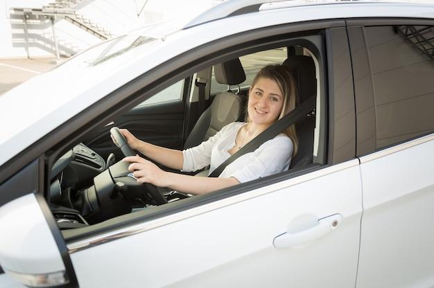 Glimlachende blonde vrouw in wit overhemd rijdende auto