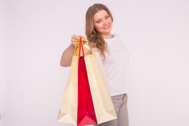 Glimlachende blonde vrouw met boodschappentassen op wit