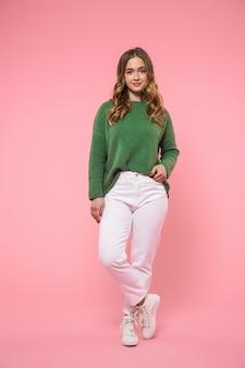 Glimlachende blonde vrouw met een groene trui, poserend met arm in zak en kijkend naar de voorkant over roze muur