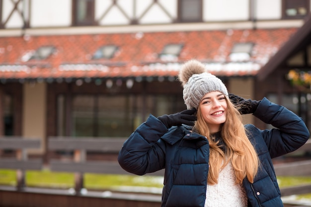 Glimlachende blonde vrouw met zwarte winterjas en gebreide muts poseren op straat in kiev