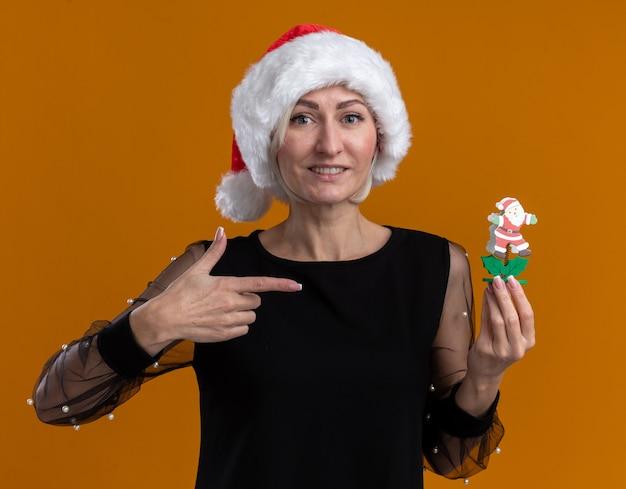 Glimlachende blonde vrouw van middelbare leeftijd met een kerstmuts die vasthoudt en wijst naar het speelgoed van de kerstman geïsoleerd op een oranje muur