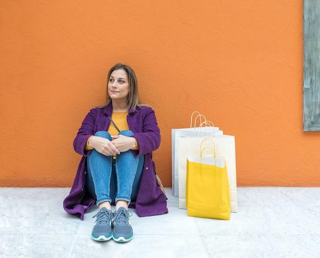 Glimlachende blonde vrouw zittend op de vloer met boodschappentassen op middelbare leeftijd