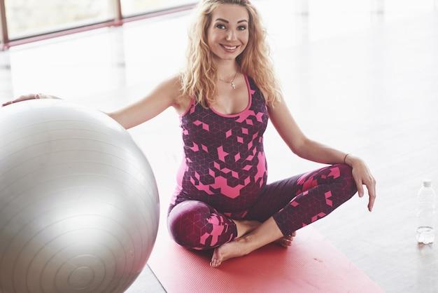 Glimlachende blonde zwangere vrouw in roze zittend op de fitnessmat met de stabiliteitsbal met de rechterhand.