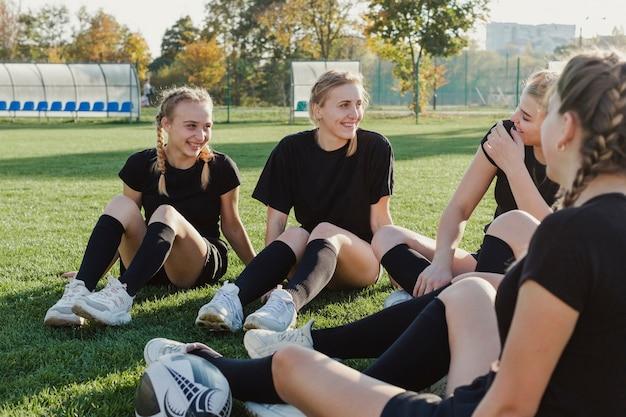 Glimlachende blondemeisjes die op gras zitten