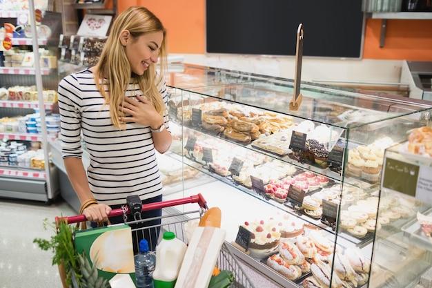 Glimlachende blondevrouw die desserts bekijken