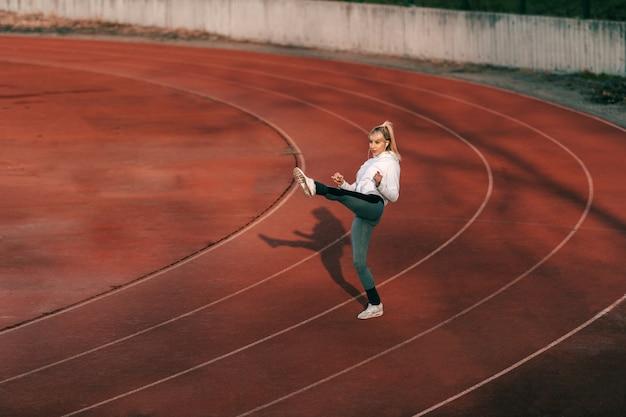Glimlachende blondevrouw die in sportkleding in de lucht schoppen terwijl status op renbaan.