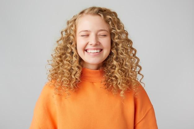 Glimlachende blondine met krullend haar, staat tevreden haar ogen te sluiten en verheugt zich