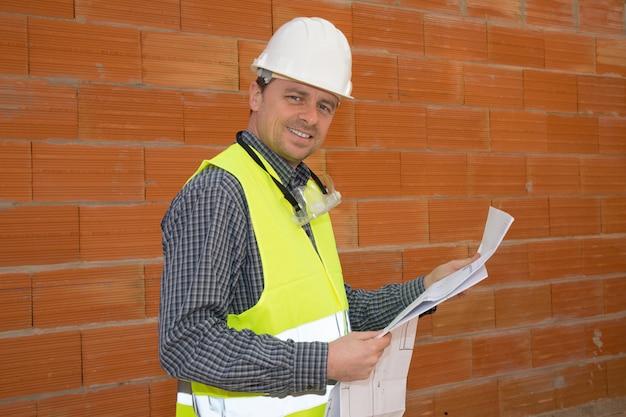 Glimlachende bouwmanager die zich op bouwterrein bevinden