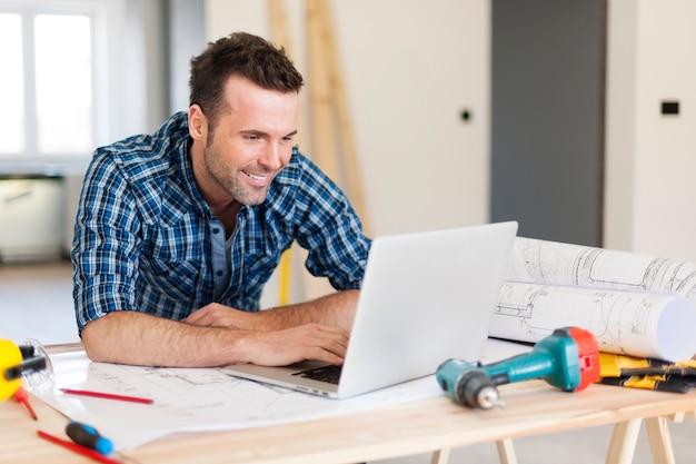 Glimlachende bouwvakker die met laptop werkt