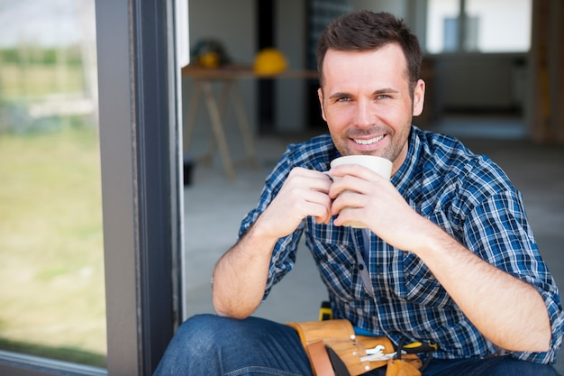 Glimlachende bouwvakker tijdens de koffierem