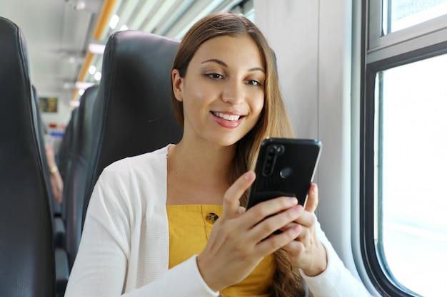 Glimlachende braziliaanse zakenvrouw met behulp van smartphone sociale media-app tijdens het woon-werkverkeer in de trein. vrouw zitten in vervoer genieten van reizen.