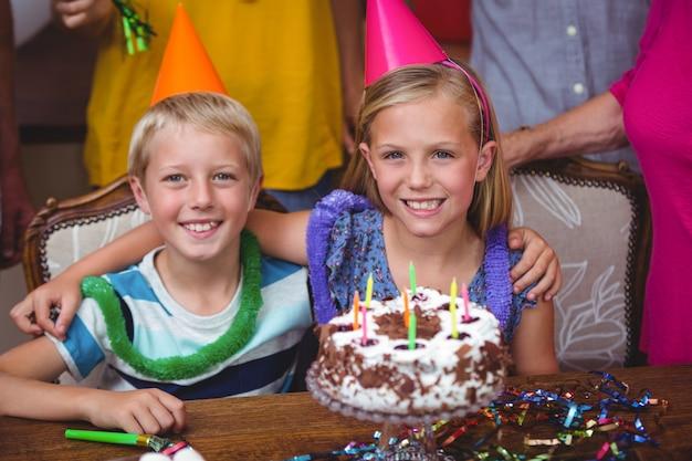 Glimlachende broers en zussen met verjaardagstaart