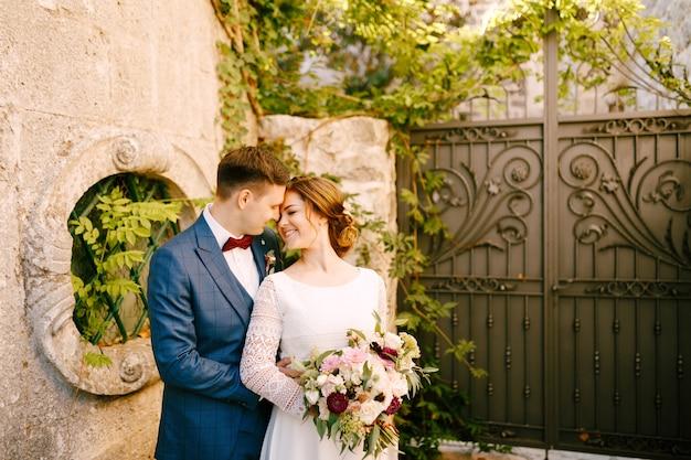 Glimlachende bruid en bruidegom knuffelen tegen smeedijzeren poorten in de tuin