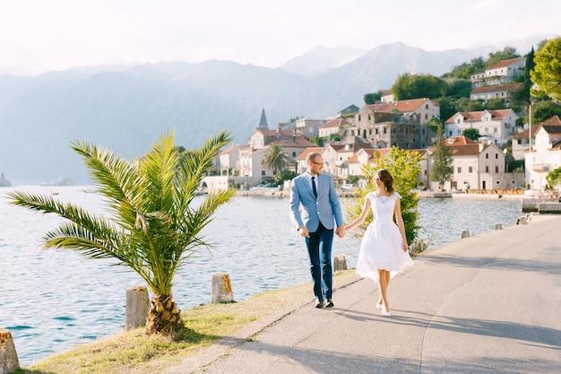 Glimlachende bruid en bruidegom lopen langs de weg hand in hand tegen de zee en de huizen