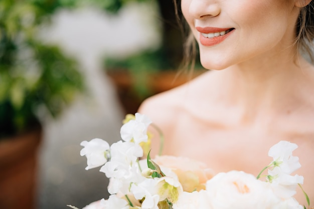 Glimlachende bruid in een mooie jurk met een boeket bloemen
