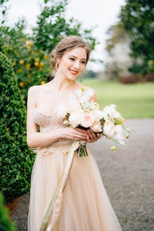 Glimlachende bruid in een roze jurk met een boeket bloemen op een achtergrond van een groene boom in een badkuip