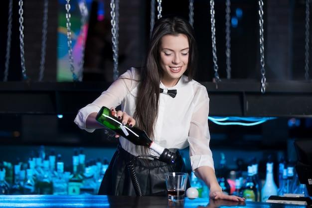 Glimlachende brunette barman serveert drank