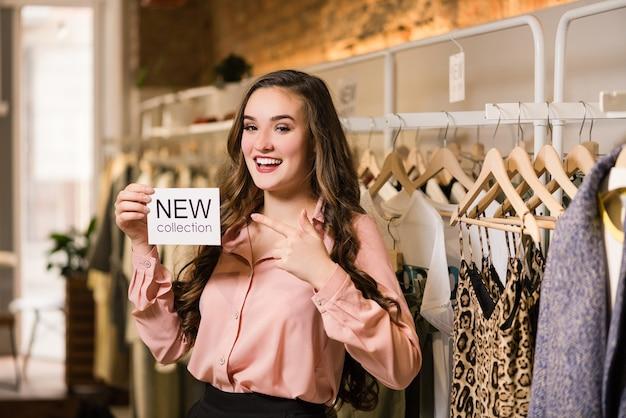 Glimlachende brunette consultant houdt nieuwe collectie-tag in petto