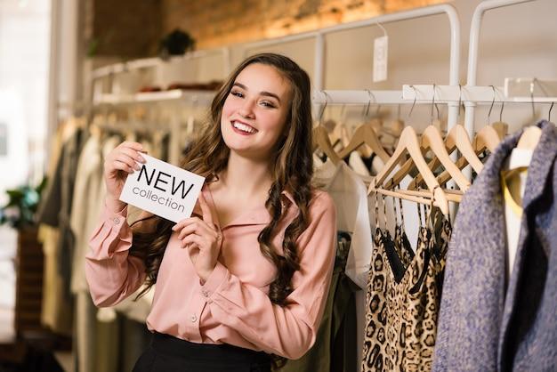 Glimlachende brunette consultant in winkel met nieuwe collectie-tag