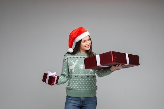 Glimlachende brunette die kerstcadeau in de arm bekijkt.