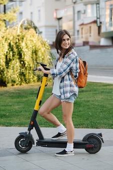 Glimlachende brunette in het park op elektrische scooter die over haar schouder kijkt