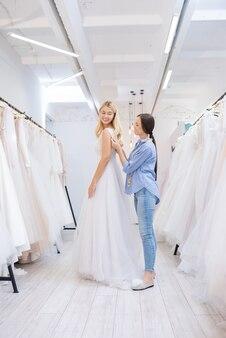 Glimlachende brunette trouwjurk kleermaker bruid bijstaan om jurk te dragen tussen rijen van mooie jassen