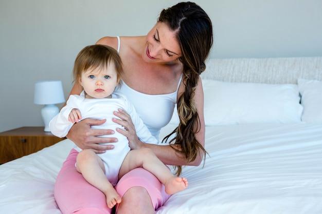 Glimlachende brunette vrouw houdt een schattige baby zittend op een bed