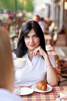 Glimlachende brunette vrouw in café koffie drinken met croissant. communicatie en vriendschap concept.