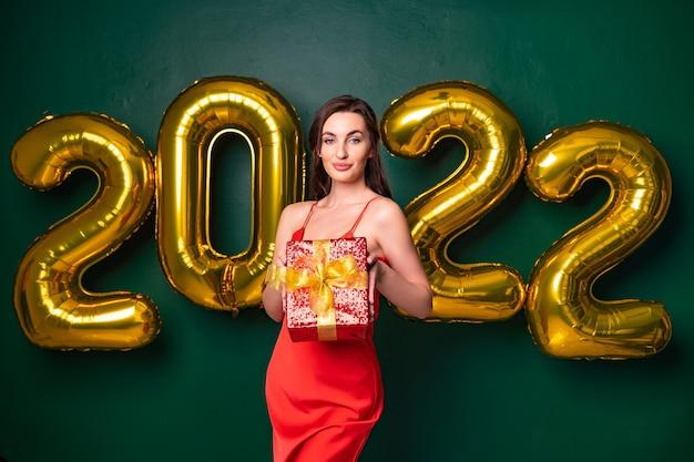 Glimlachende brunette vrouw in rode jurk heft de rode geschenkdoos op met gouden luchtballonnen voor het nieuwe jaar
