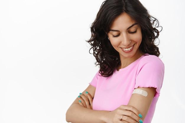 Glimlachende brunette vrouw kijkend naar medische pleister op haar schouder, werd gevaccineerd met vaccin van sars cov coronavirus, vaccinatieconcept