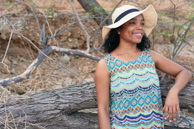 Glimlachende brunette vrouw met hoed in de open lucht op zoek naar één kant