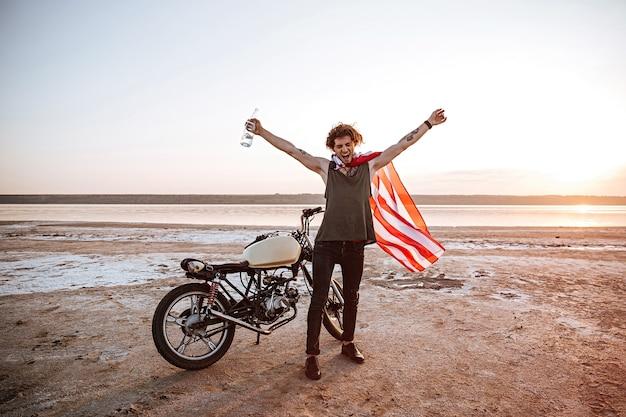Glimlachende brutale man in kaap van de amerikaanse vlag zittend op zijn motorfiets met handen in de lucht