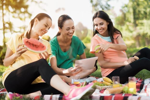 Glimlachende buikvrouwen. zwangere vrouwen kijken tablet.