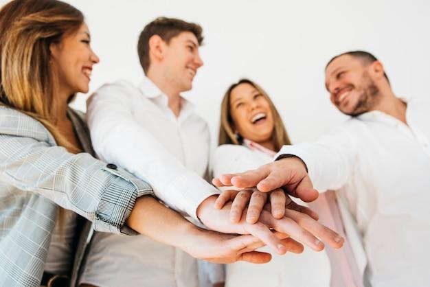 Glimlachende bureaucollega's die handen samenbrengen