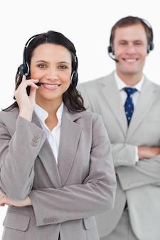 Glimlachende call centre-agenten met opgezette hoofdtelefoons en wapens