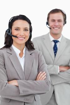 Glimlachende call centreagenten met hoofdtelefoons en gevouwen wapens