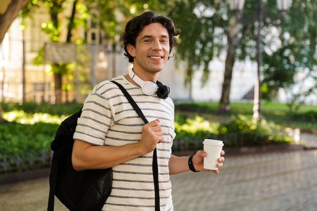 Glimlachende casual jongeman koffie drinken
